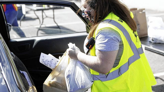 Volunteer Heather Brokaw of Grove City hands out goods to customers at the Grove City Farmers Market on May 30 n the parking lot behind the businesses on Broadway between Park Street west of Broadway and Grant Avenue.