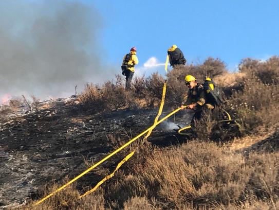 Firefighters battled a blaze that burned along Highway