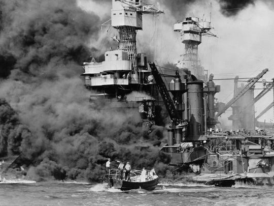 In this Dec. 7, 1941 photo made available by the U.S. Navy, a small boat rescues a seaman from the USS West Virginia burning in the foreground in Pearl Harbor, Hawaii, after Japanese aircraft attacked the military installation. More than 2,300 U.S. service members and civilians were killed in the strike which brought the United States into World War II. (U.S. Navy via AP)
