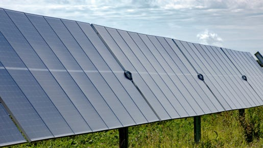 Solar panels lined up in a field.