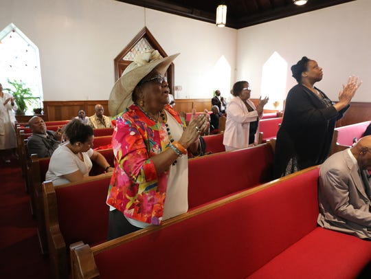 Congregants sing during the Sunday service at St. Charles
