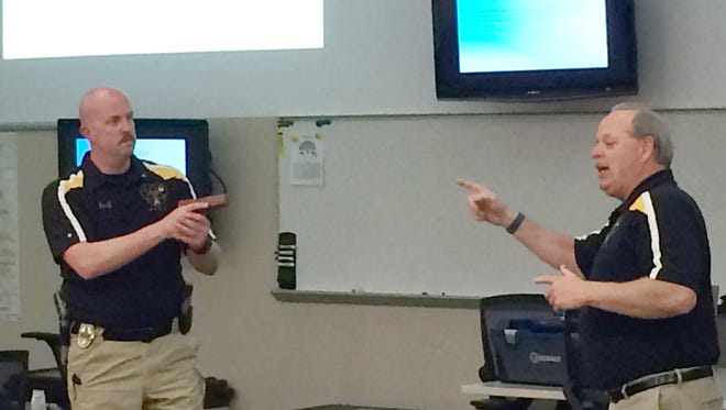 University of Iowa police officers Jess Bernhard, left, and Joe Lang demonstrate how to twist away an active shooter's gun on Monday night.