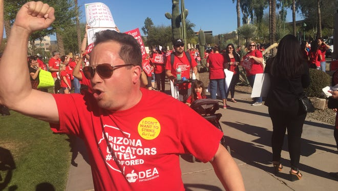 """A man leads a chant of """"overworked, underpaid!"""" at the Capitol on March 28, 2018."""