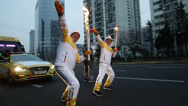 SEOUL, SOUTH KOREA -- Torch bearers pose with the PyeongChang 2018 Winter Olympics torch during the PyeongChang 2018 Winter Olympic Games torch relay on Jan. 16, 2018, in Seoul, South Korea.