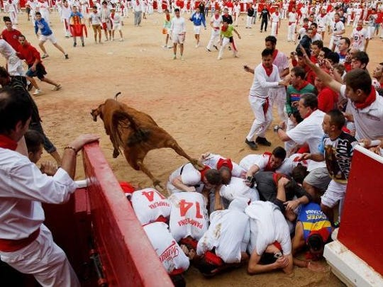 A bull leaps over crouched runners and into the ring in Pamplona.
