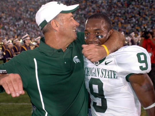 Michigan State coach John L. Smith, left, celebrates with Demond Williams after their overtime win over Notre Dame, Saturday, Sept. 17, 2005, in South Bend, Ind. Michigan State won, 44-41.