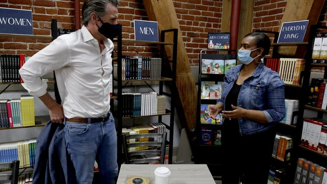 Gov. Gavin Newsom talks with Gwen Overton, owner of Legendary Coffee and Books in Stockton on Thursday during a stop on his listening tour. Newson and Stockton Mayor Michael Tubbs met with Overton and other small business owners and discussed the coronavirus and racial injustice.