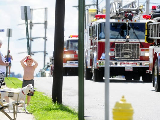 Tanner Parks, of North York, clutches his red fire helmet as various fire vehicles parade past him. The York County Fire Association Convention Parade returns Saturday.
