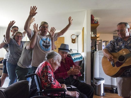 """In this Tuesday, Aug. 21, 2018 photo Don West, center, sings and claps along to the song """"You are my Sunshine,"""" at Golden Days II Adult Foster Care nursing home in Charlotte, Mich., as friends and family dance behind them."""