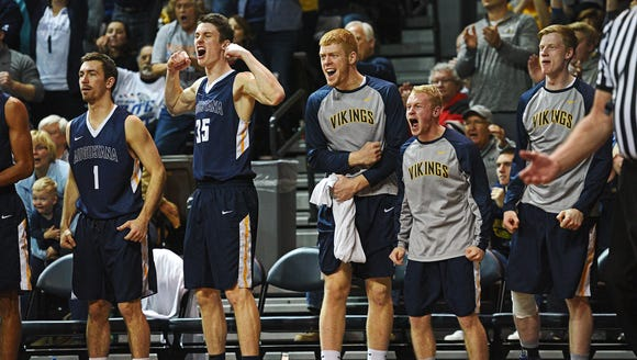 Augustana players celebrate from the bench after a