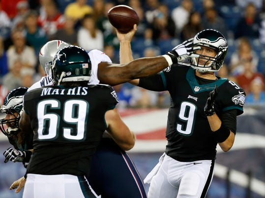 Philadelphia Eagles quarterback Nick Foles (9) passes over the arm of New England Patriots defensive tackle Vince Wilfork during the first quarter of an NFL preseason football game Friday, Aug. 15, 2014, in Foxborough, Mass. (AP Photo/Elise Amendola)