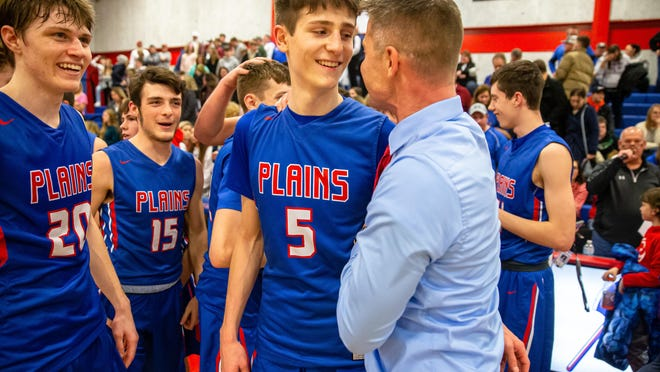 Pleasant Plains' Justin Guernsey (5) celebrates with Pleasant Plains boys basketball head coach Kyle Weber after the Cardinals won the Sangamon County Boys Basketball Tournament at Lincoln Land Community College's Cass Gymnasium , Saturday, Jan. 18, 2020.