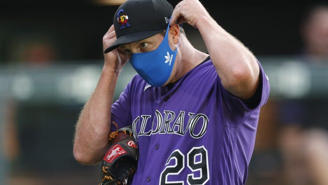 Colorado Rockies relief pitcher Bryan Shaw puts on his face mask after taking part in drills during the team's practice on Friday.