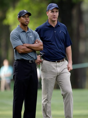 Tiger Woods, left, and then-Indianapolis Colts quarterback Peyton Manning, right, wait to hit on the fifth fairway during the pro-am of the 2009 Quail Hollow Championship golf tournament.