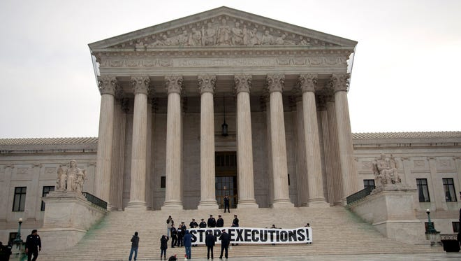 Demonstrators hold a banner on the steps of the Supreme Court on Jan. 17, 2012, during a protest against the death penalty.