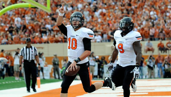 Oklahoma State Cowboys quarterback Clint Chelf (10) and fulback Desmond Roland (9) celebrate after a touchdown against the Texas Longhorns during the first quarter at Darrell K Royal-Texas Memorial Stadium.