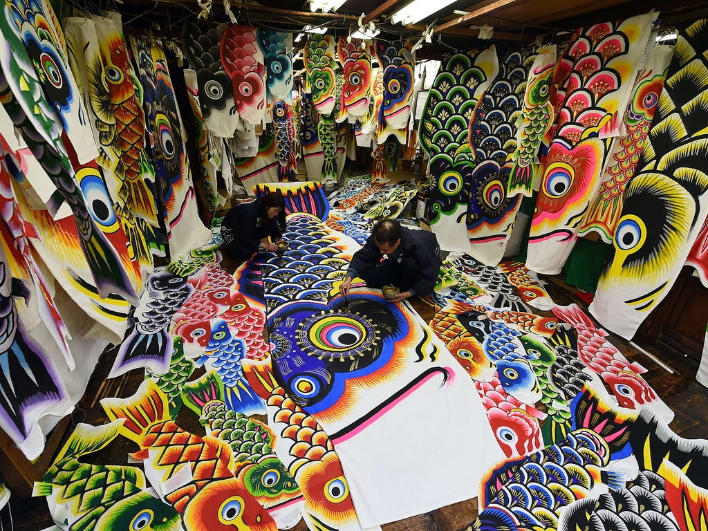 Workers paint a carp streamer for the upcoming Children's Day celebration at the Hashimoto Yakichi factory on April 15 in Kazo, Japan.