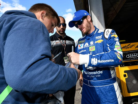 Dale Earnhardt Jr., right, signs for a fan before practice for the NASCAR Cup series auto race, Saturday, Sept. 30, 2017, at Dover International Speedway in Dover, Del. (AP Photo/Nick Wass)