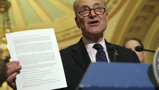 Senate Minority Leader Charles Schumer of N.Y., holds up a letter to Republicans about healthcare while speaking to the media, Tuesday, May 9, 2017, on Capitol Hill in Washington. (AP Photo/Jacquelyn Martin)