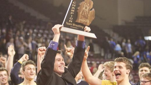 Hartland head coach Todd Cheney hoists the Division 1 wrestling  team championship after the Eagles won it for the first time in 2016. It was the No. 1 sports story of 2016.
