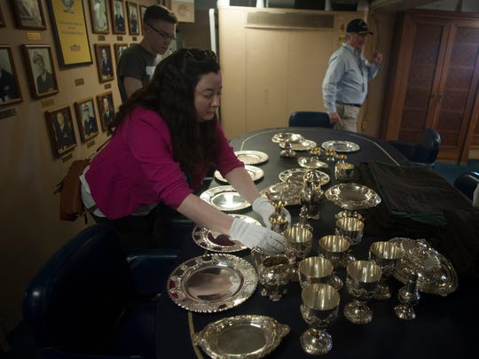 Battleship New Jersey staffer Jennnifer Lon unpacks items from a Tiffany & Co. silver service given to the ship for the captain's quarters.
