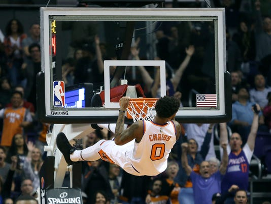 Phoenix Suns forward Marquese Chriss hangs from the rim after dunking against the San Antonio Spurs during the second half of an NBA basketball game Saturday, Dec. 9, 2017, in Phoenix. The Spurs defeated the Suns 104-101. (AP Photo/Ralph Freso)