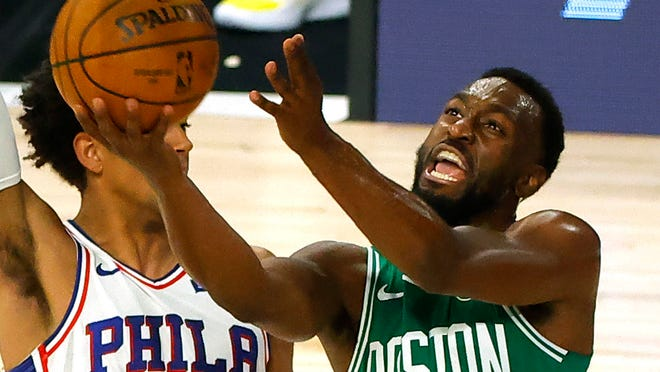 Kemba Walker, right, of the Boston Celtics goes up for a shot against the Philadelphia 76ers during the first half of Game 2 of an NBA basketball first-round playoff series, Wednesday, Aug. 19, 2020, in Lake Buena Vista, Fla.