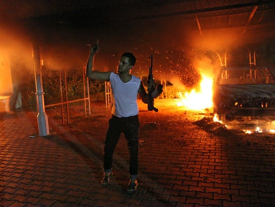 A man waves a rifle as buildings and cars are engulfed