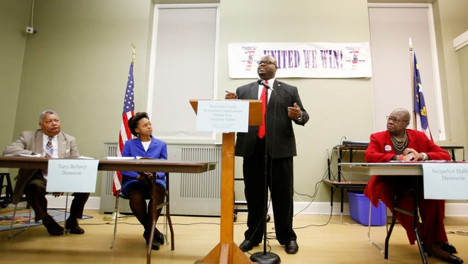Keith Young speaks at the podium as fellow candidates, from left, Alfred Whitesides, Jr., Terry Bellamy and Jacquelyn Hallum listen during the Buncombe County Democratic Commissioner District One Candidate Forum at Stephens Lee Recreation Center December 1, 2016.