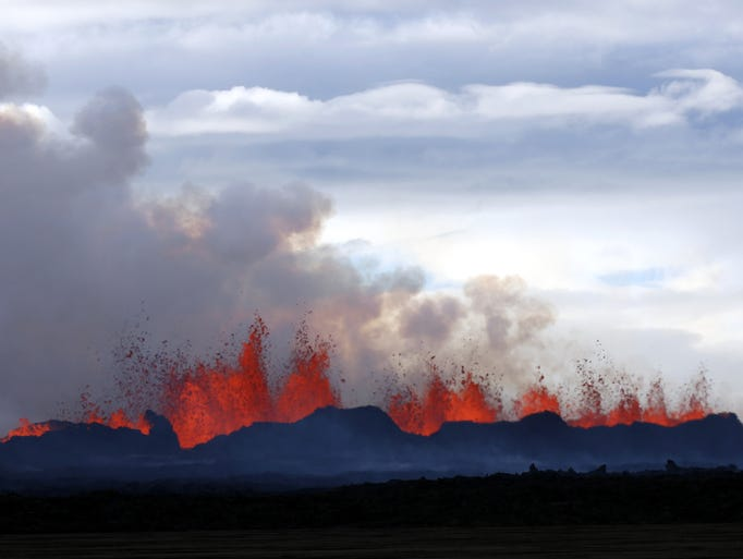 A plume of smoke rises from the lava eruption on Holuhraun, northwest of the Dyngjujoekull glacier in Iceland, Monday, Sept. 1, 2014.  Lava fountains danced along a lengthy volcanic fissure near Iceland's subglacial Bardarbunga volcano Sunday, prompting authorities to raise the aviation warning code to the highest level and close the surrounding airspace. The warning was lowered 12 hours later as visibility improved and it was clear that no volcanic ash was detected. (AP Photo/Eggert Johannesson)