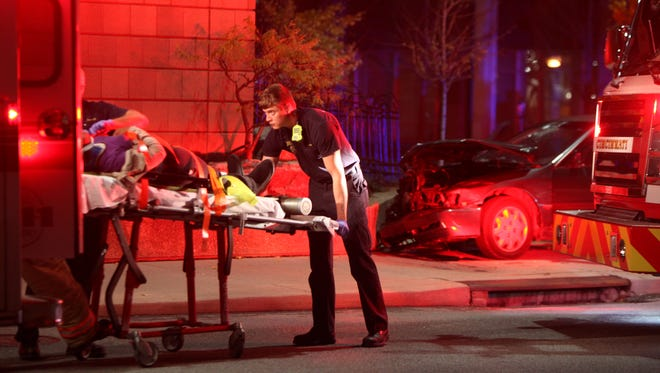 Emergency crews transport a woman from scene of a two-vehicle accident on 7th and Plum streets Tuesday night. Two women suffered minor injuries and were taken to University of Cincinnati Hospital Medical Center.