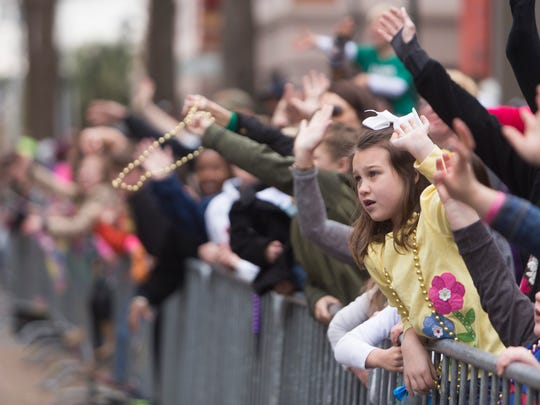 Children lean over a barricade to catch beads during