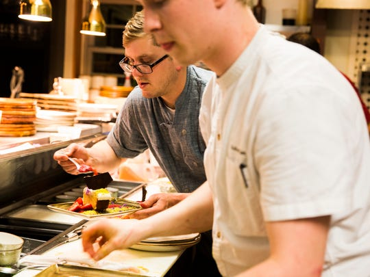 Owner/chef  Ryan Trahan, left, garnishes a fruit berry