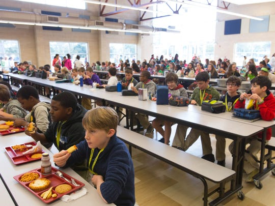 """Students at LJ Alleman Middle School eat lunch in their new """"cafetorium,"""" a combination cafeteria and auditorium."""
