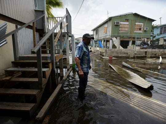 Juana Matos resident Hector Rosa walks through a flooded