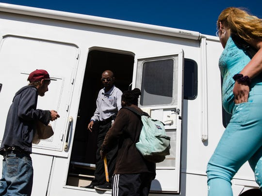 Alfred Gibson, standing in the doorway of the Camden Area Health Education Center Mobile Health Van greets people who came to receive a packet of basic necessities in Camden, N.J.
