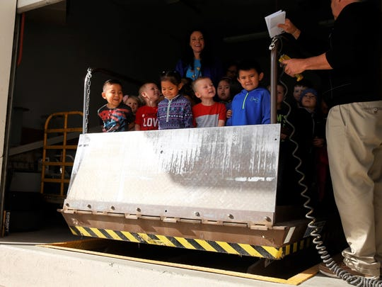 Students from Kirtland Early Childhood Center react as the mail lift rises during a tour of the post office in Kirtland on Tuesday.