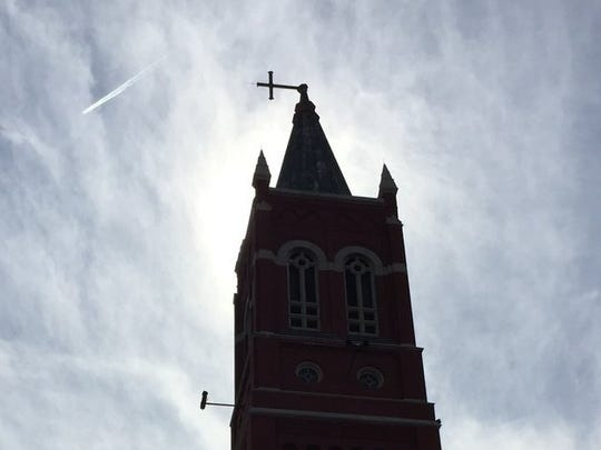 The cross atop St. Mary's Church in Rochester appears ready to topple. The street is blocked. Staff waiting for help.