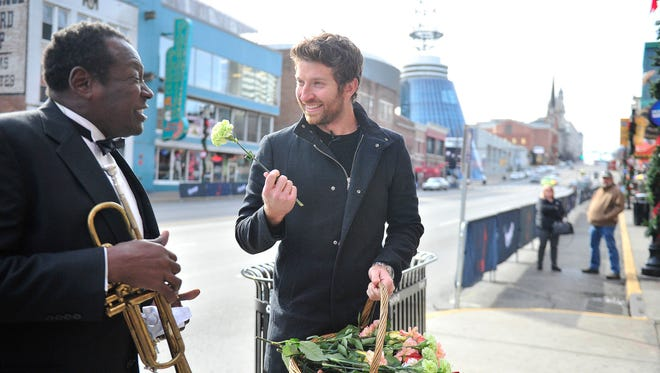 """Brett Eldredge took to the streets to hand out flowers on Monday in Nashville. Here, Eldredge sings with Ken Dorsey on Broadway and gives him a flower. The two sang """"When the Saints Go Marching In."""""""
