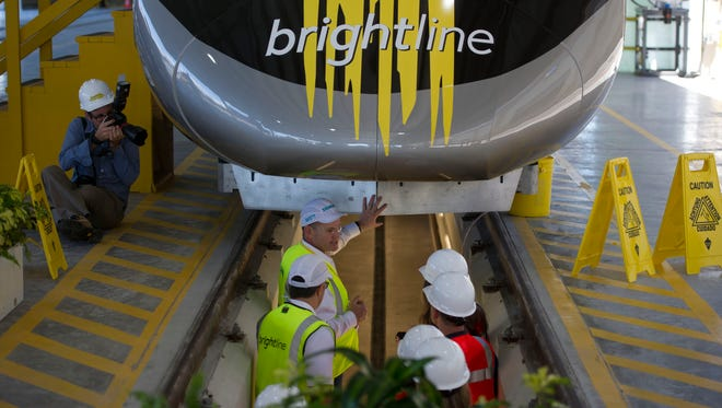 "Siemens Rolling Stock president Michael Cahill (center) leads a group through the maintenance pit underneath Brightline's ""BrightBlue"" locomotive during a tour of the new train Jan. 11, 2017, in West Palm Beach. Siemens manufactured the train in Sacramento, Calif., before moving it to the South Florida facility."