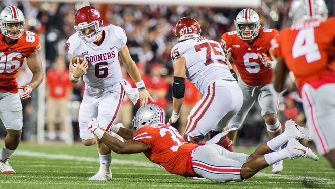 Oklahoma Sooners quarterback Baker Mayfield tries to break free of Ohio State Buckeyes linebacker Malik Harrison.