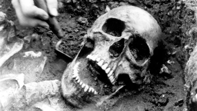 An archaeologist uncovers the skeleton of one of more than 1000 bodies discovered on the site of the Old Royal Mint near the Tower of London, in England, in 1987. The person is suspected to have died during the Black Death which killed nearly half of London's population in 1349. (AP Photo) ORG XMIT: APHSL756103 [Via MerlinFTP Drop]
