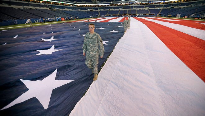 Pvt. Dylan Pitcock, with the 519th Indiana Army National Guard of Terre Haute, and others finished putting together the football-sized American flag covering the Indianapolis Colts football field at Lucas Oil Stadium, before the Colts played the New Orleans Saints on Oct. 25, 2015.