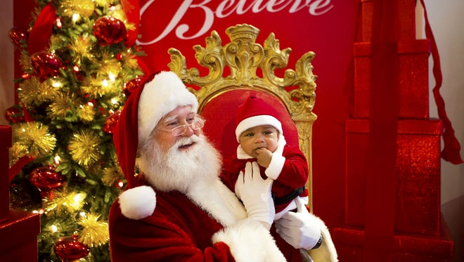 Damian Thomas, 5 months, meets Santa Claus for the first time at Macy's on Vine Street Friday, Dec. 18, 2015.