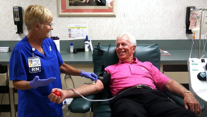 """Registered nurse Kathy Moore, left, prepares Bill Hall, 75, before he donates his 438th pint at the NCH Community Blood Center in Naples on Monday, April 18, 2016. Hall has been donating blood since 1960. """"You give a gift of good health to somebody that is hurting,"""" Hall says."""