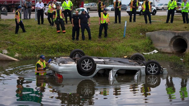 A firefighter searches a submerged car in a canal near the intersection of Airport-Pulling and Pine Ridge Roads after it was involved in a two-car accident on Monday, May 16, 2016, in Naples. North Collier Fire Control and Rescue District spokesman Jerry Sanford said the driver of the submerged car was taken to the hospital with injuries.