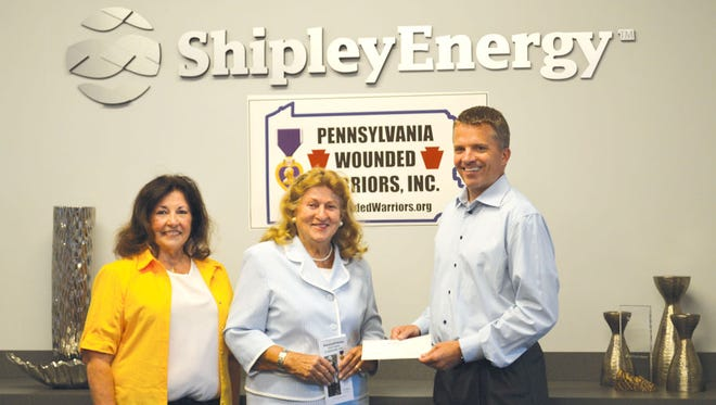 Victoria Caparella, left, and Helen Sajer, center, from Pennsylvania Wounded Warriors, Inc. receive a donation of $1,840 from Shipley Energy CEO Dave Gruno.