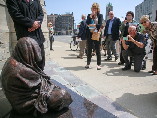 Members of the congregation observe the bronze statue