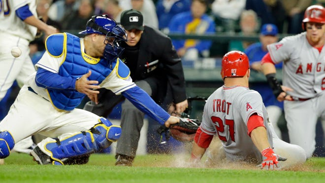 Seattle Mariners catcher Chris Iannetta, left, bobbles the ball as Los Angeles Angels' Mike Trout slides safely into home in the eighth inning of a baseball game, Sunday, May 15, 2016, in Seattle. Trout scored on a two-run single by Angels' Daniel Nava.