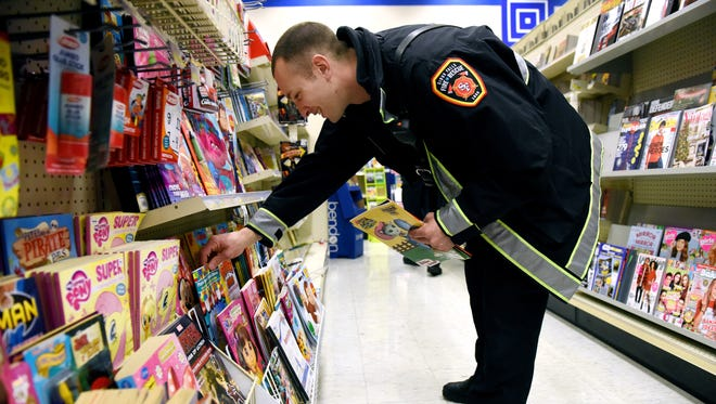 Zach Weisenburger with Sioux Falls Fire Rescue shops for books in Lewis Drug at the 41st St. and Minnesota Ave. location on Friday morning. The fire department will deliver the toys to children at Avera, Sanford, and Lifescape on Christmas Eve.